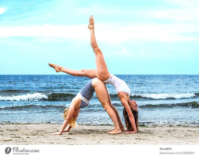two young girls in white top and black bottom on the sandy shore acrobatic acrobatic yoga active asana beach blond blue body brown-haired calm coast