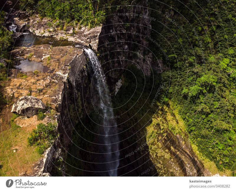 Aerial top view perspective of amazing 500 feet tall waterfall in the tropical island jungle of Mauritius. river cliff mauritius forest africa flowing green