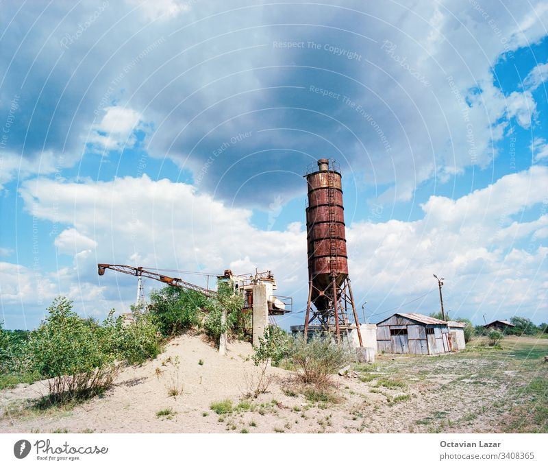 Old abandoned silo and industrial machine, building, sand, clouds, blue sky storage farm container rural wheat grain agriculture metal industry tower