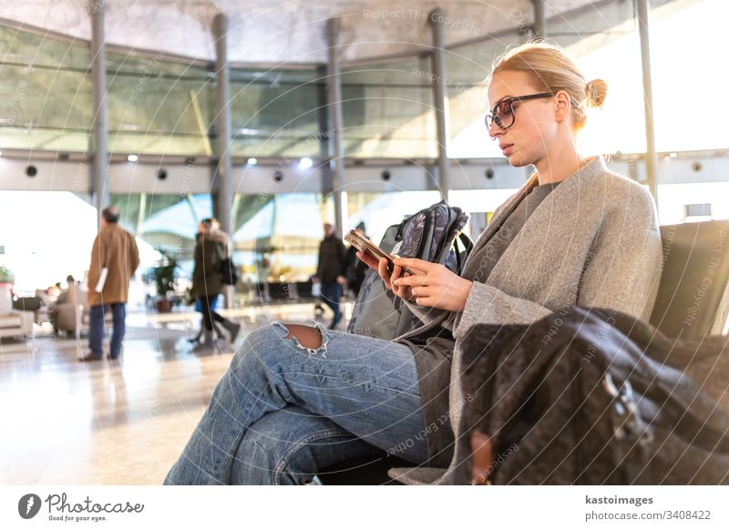 Female traveler using her cell phone while waiting to board a plane at departure gates at airport terminal. female woman business flight baggage luggage young
