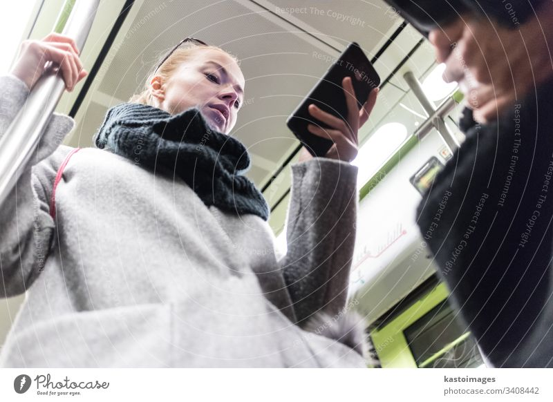 Beautiful blonde woman wearing winter coat and scarf reading on the phone while traveling by metro public transport. subway city passenger female urban train