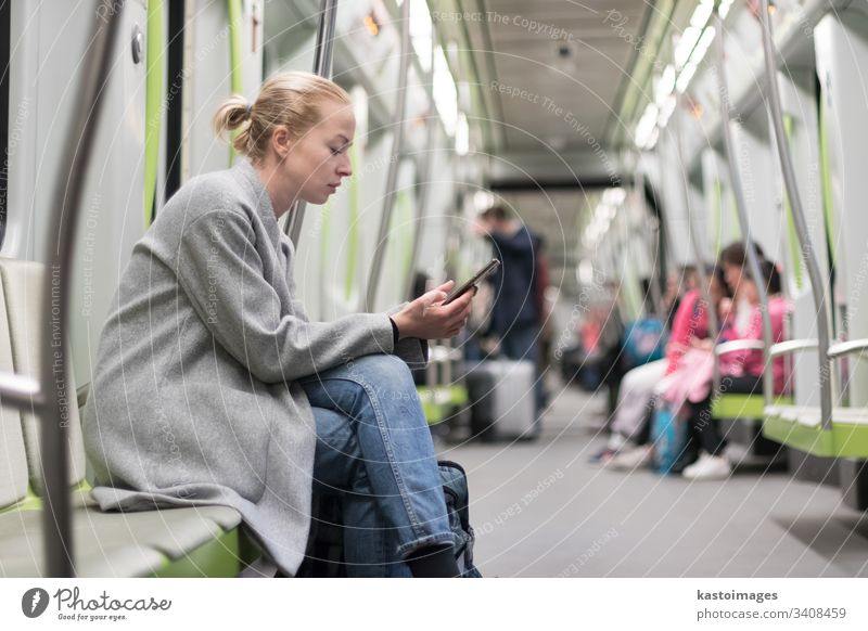 Beautiful blonde woman wearing winter coat reading on the phone while traveling by metro public transport. subway city passenger female urban train sitting