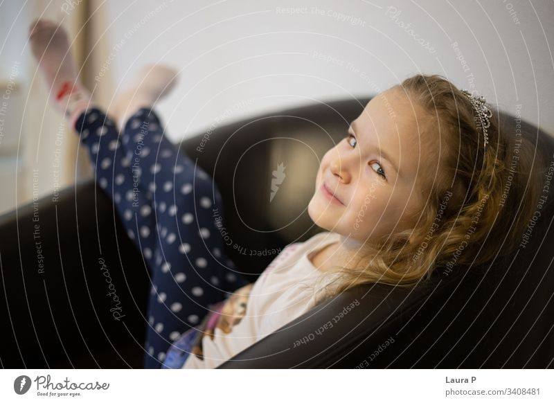 Happy blonde little girl relaxing in an armchair relaxation daughter classic alone happiness family sit comfort cozy resting play cheerful smile comfortable