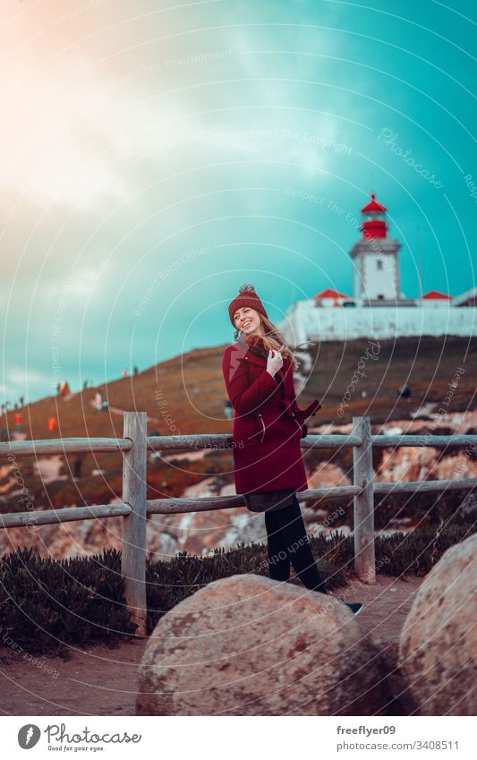 Woman standing in front of Cabo da Roca Lighthouse in Sintra, Portugal woman one laughing atlantic water scenic landmark edge navigation marin light cliff space