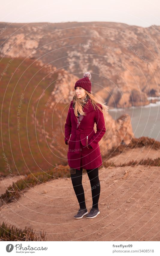 Young woman on a red coat contemplating the sea from the top of a cliff one standing atlantic water scenic landmark edge marin light space Sintra safety beauty