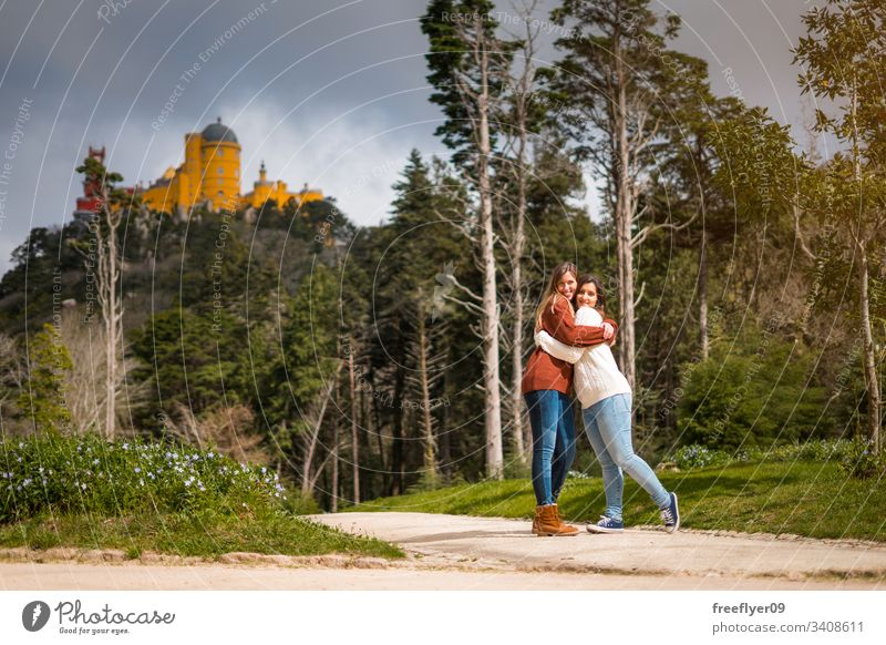 Two friends hugging in front of Pena Palace in Sintra, Portugal building national landmark europa portugal history traditional sintra tree antique mountain