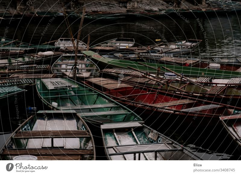 Many colourful little empty rowboats close together made of wood on the water Rowboat Wood variegated Oar Asia Exterior shot Water Colour photo Lake Trip