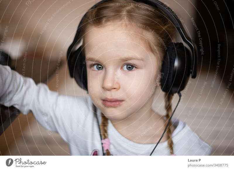 Close up of beautiful blonde little girl listening to music at headphones close up child green eyes Listen to music Relaxation Child To enjoy Joy happiness
