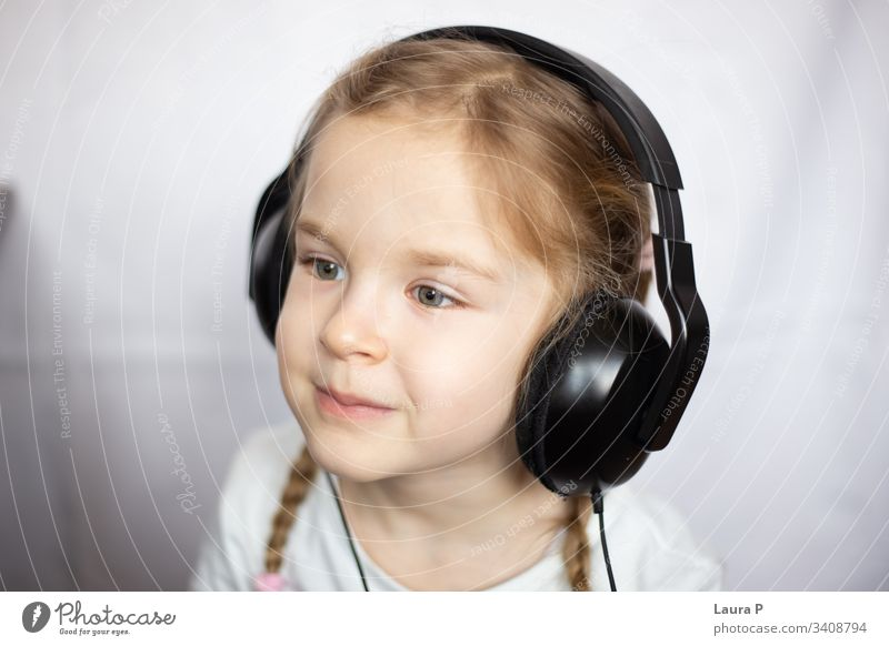 Close up of a beautiful blonde little girl listening to music at headphones smile happy young beauty child kid daughter fun cute enjoy isolated person