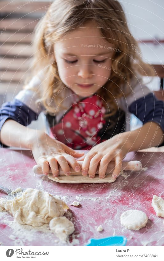 Beautiful blonde little girl playing with dough beautiful curly hair baking cooking rolling pin close up hands sweets delicious home-made cute adorable