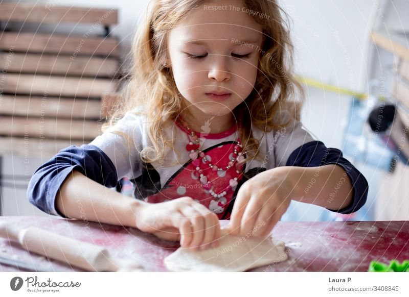 Beautiful blonde little girl playing with dough beautiful curly hair cooking baking table doughtnuts Baked goods Dough Baking Colour photo Flour Food home made