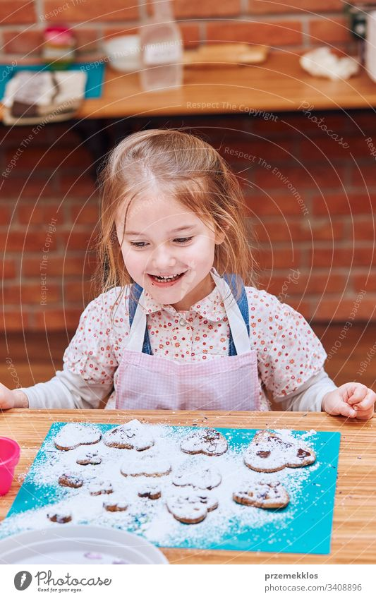 Little girl happy because of her baked cookies. Decorating cookies with colorful sprinkle and icing sugar. Kid taking part in baking workshop. Baking classes for children, aspiring little chefs. Learning to cook. Combining and stirring prepared ingredients