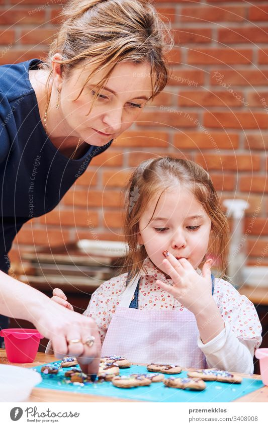 Little girl with her mom's help decorating baked cookies with colorful sprinkle and icing sugar. Kid taking part in baking workshop. Baking classes for children, aspiring little chefs. Learning to cook. Combining and stirring prepared ingredients