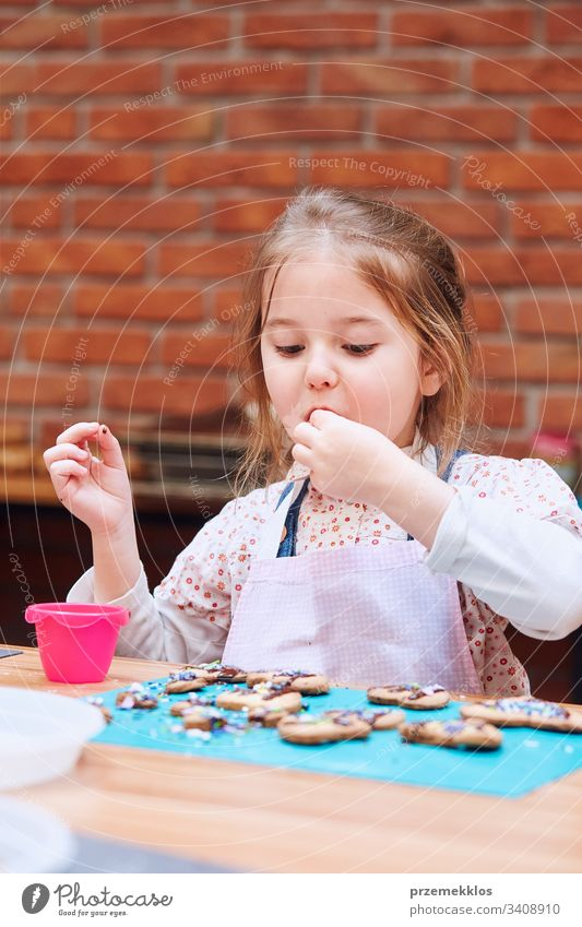 Kid taking part in baking workshopLittle girl tasting cookie baked oneself. Decorating her baked cookies with colorful sprinkle and icing sugar. Kid taking part in baking workshop. Baking classes for children, aspiring little chefs. Learning to cook