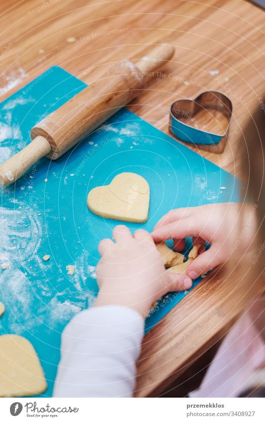 Little girl cutting the dough to heart shapes for the cookies. Kid taking part in baking workshop. Baking classes for children, aspiring little chefs. Girls learning to cook. Combining and stirring prepared ingredients. Real people, authentic situations