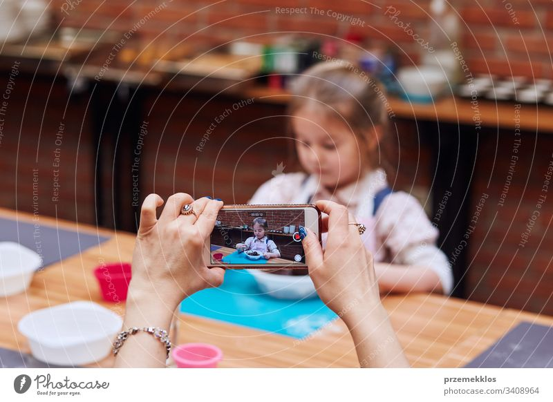 Mom recording her little daughter while taking part in baking workshop. Baking classes for children, aspiring little chefs. Learning to cook. Combining and stirring prepared ingredients. Real people, authentic situations