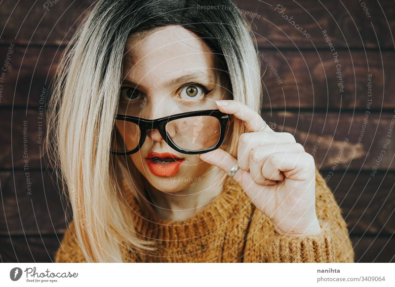 Close portrait of a beautiful nerdy woman glasses eyewear fashion trendy model blonde rimmed glasses ombre hairstyle cool attractive pretty face accessories