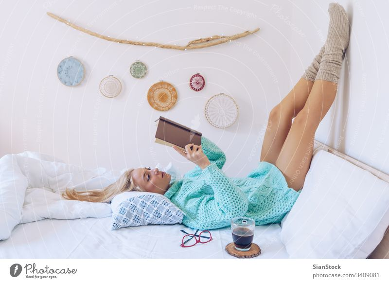 Young woman lying in bed while reading a book girl coffee sweaters white beautiful glasses morning home bedroom blonde wall pillows blanket blankets