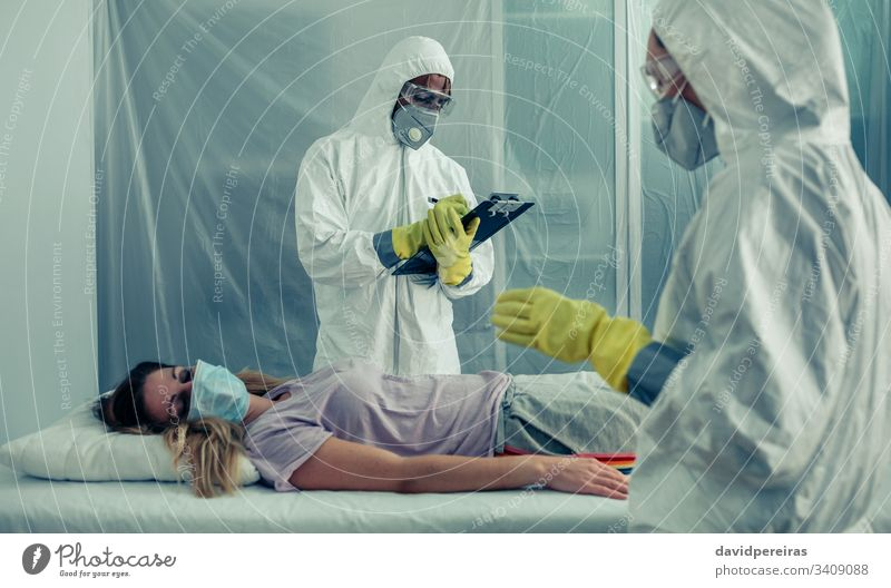 Doctors with bacteriological protection suits examining a patient isolation quarantine medical check covid-19 coronavirus respiratory virus treatment doctor