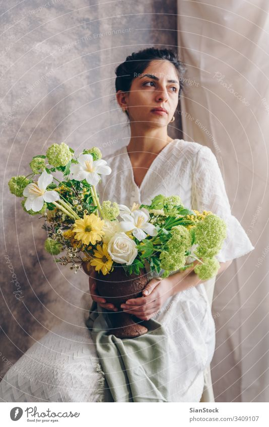 Young woman in a white dress holding vase with flowers. Vintage, romantic concept. bouquet girl metal sit sitting chair soft light beautiful vintage wedding