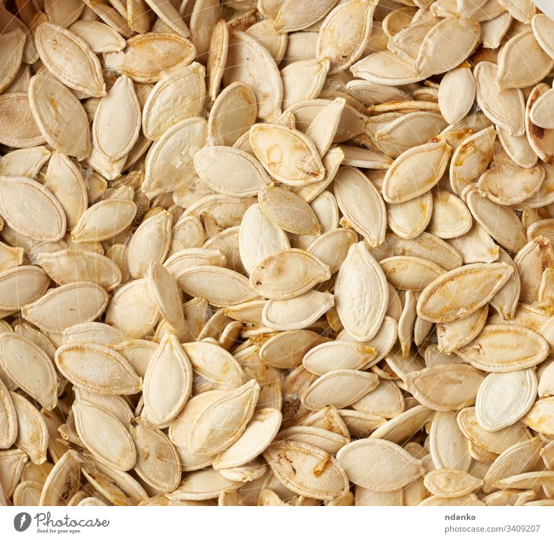 dry raw pumpkin seeds, full frame food healthy vegetarian background organic vegetable fresh diet white meal nutrition natural yellow ingredient delicious snack