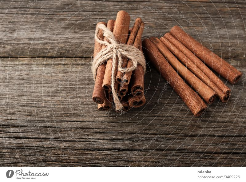 brown cinnamon sticks tied in a bun on a gray wooden background, tasty and fragrant spice food sweet ingredient closeup dessert aroma aromatic table healthy