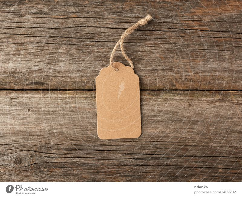 Empty brown paper tag tied with white string. Price tag, gift tag wooden gray address background blank business buy card cardboard cord coupon craft design