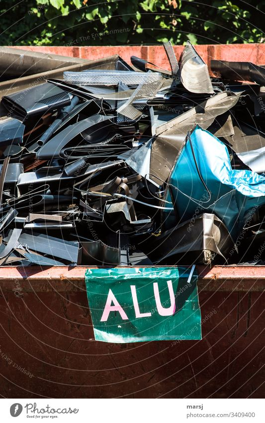 A scrap container full of, partly coloured, aluminium scrap from a roofer. In the front a board with the inscription Alu Scrap metal Aluminium variegated
