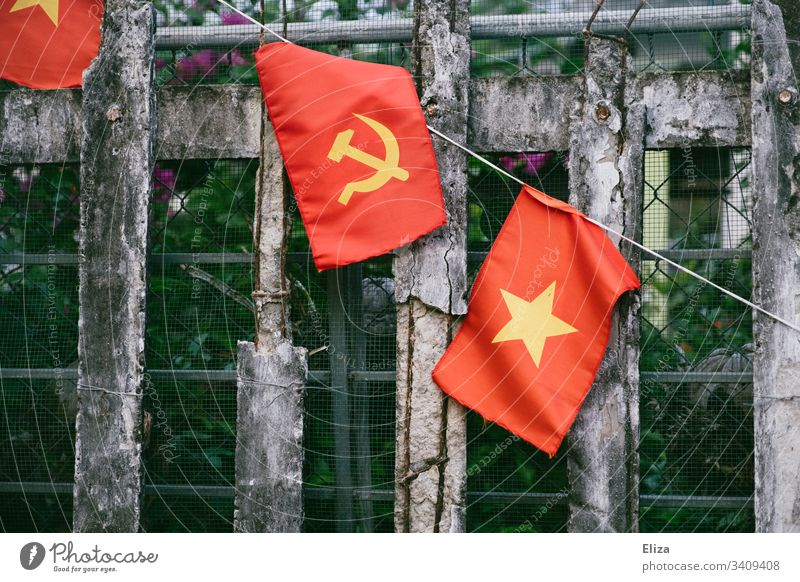 A fence on which the Vietnamese national flag, with hammer and sickle in yellow on a red background, hangs; symbol of communism Communism Socialism Ensign