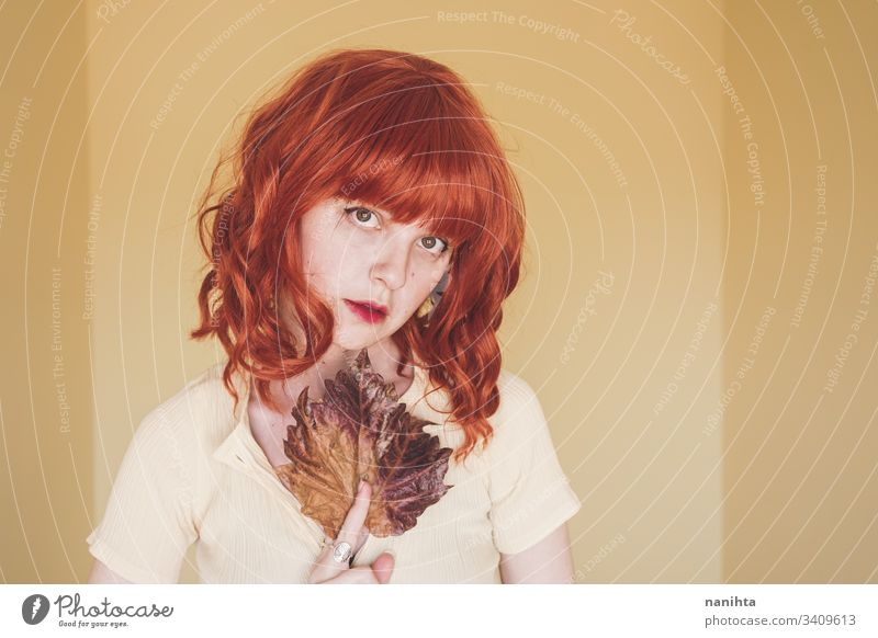Redhead young woman covering by a dry autumn leaf fall leave portrait art artistic redhead red hair delicate face ginger concept conceptual youth orange yellow
