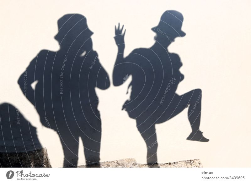 two shadow people Shadow Shadow person fun Funny Distorted Hat summer fun Happiness Happy Smiling Lifestyle silhouette at the same time free time Together