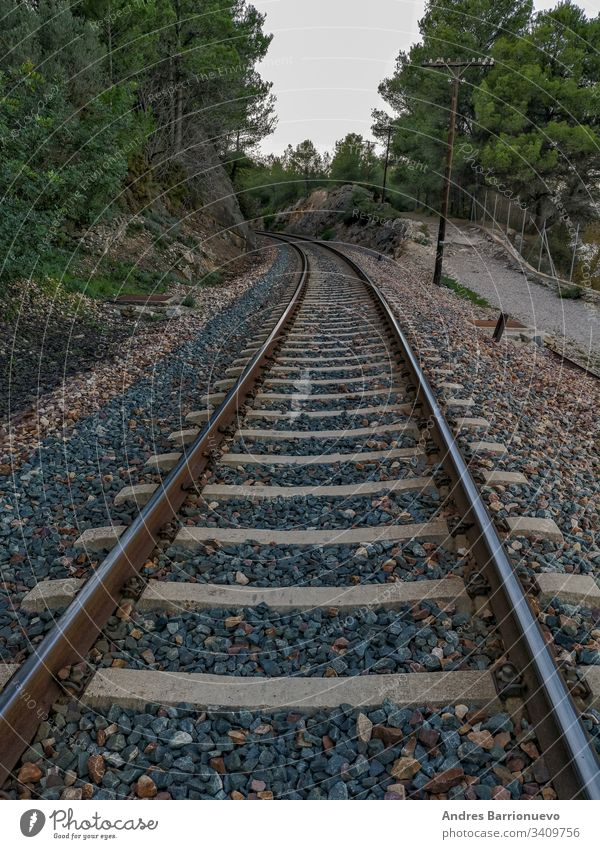 Train track through the mountain rock gorge business outdoor curving industry wood park cargo travel rail iron sign country direction gravel cloudy