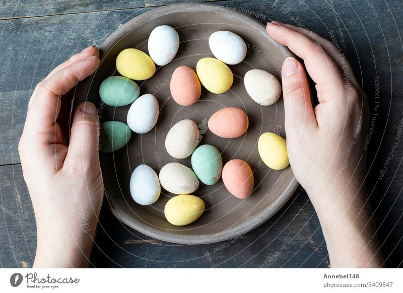 Hands holding stylish pastel painted easter eggs in ceramic grey plate on vintage old wooden background, Happy Easter holiday spring traditional symbol food