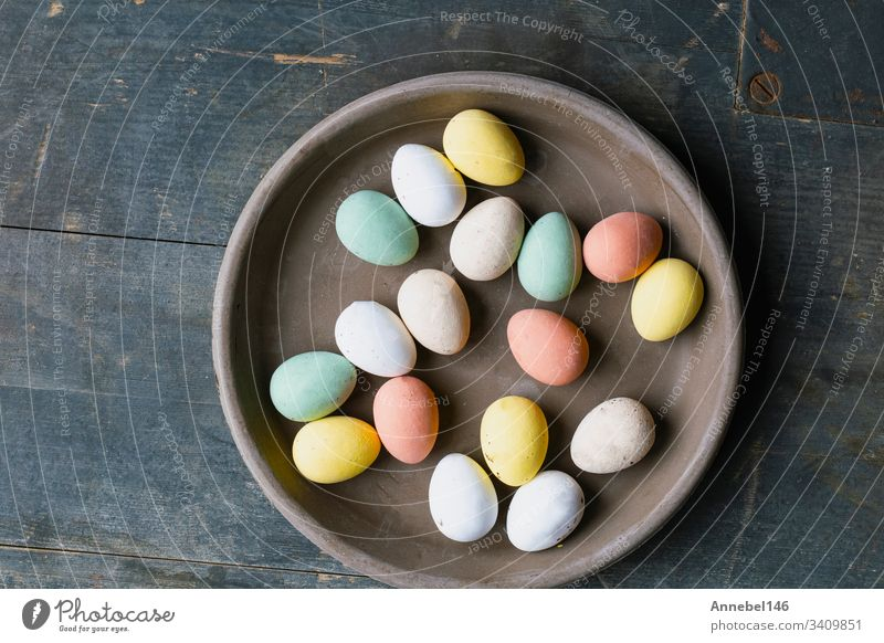 Grey Ceramic Plate with painted Easter Eggs of pastel colors on vintage wooden background. Happy Easter card concept, minimalistic design, top view spring