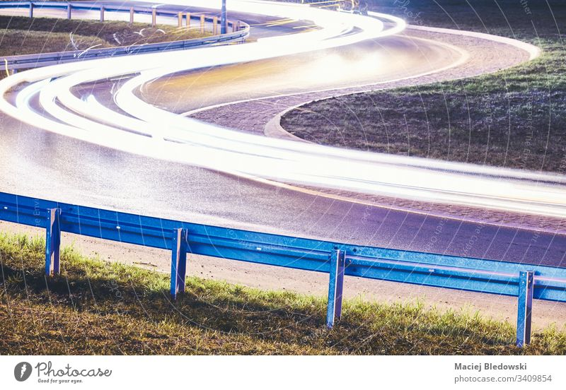 Curvy road with car light trails at night. street speed city drive guardrail safety highway steel danger DUI barrier background drunk driving concept toned
