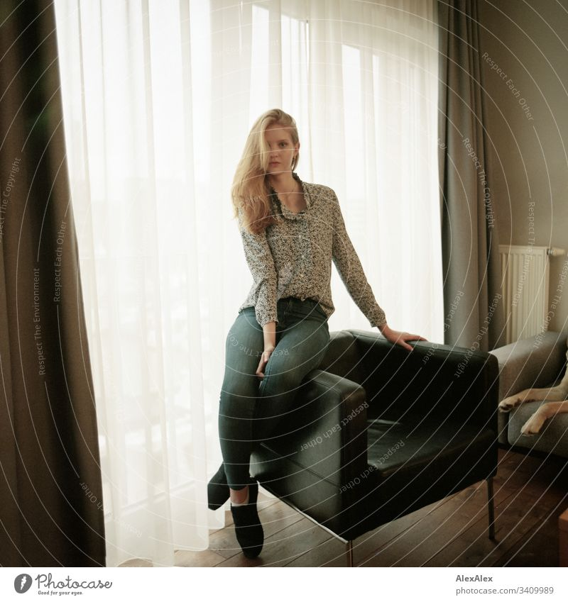 Portrait of a young woman on an armchair in front of the window Woman Girl Blonde Beautiful youthful Slim daintily Elegant Lifestyle dwell Flat (apartment)