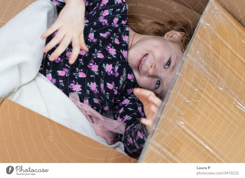 Little blonde girl hiding in a cardboard box peek a boo hide and seek family fun happiness happy enjoy laughing small interior floor playful unpacking surprise
