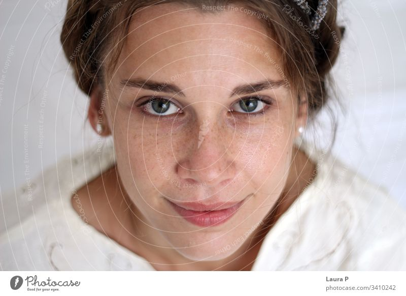 Young smiling woman with braided hair, dressed in white young face natural look close up portrait green eyes peaceful nice beautiful beauty fresh silent
