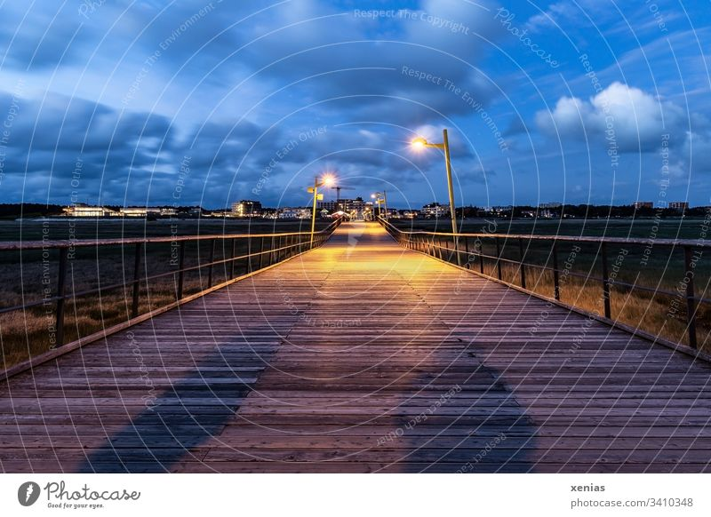 footbridge in St.Peter-Ording at dusk with big and small shadow Footbridge Twilight wood Shadow persons Coast Blue Sky lamps Clouds Deep depth of field