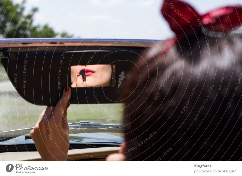 Woman rubbing lipstick in the car Lipstick Red vintage Rear view mirror car mirrors Make-up Mirror Convertible Hand fingernails Nail polish Landscape format