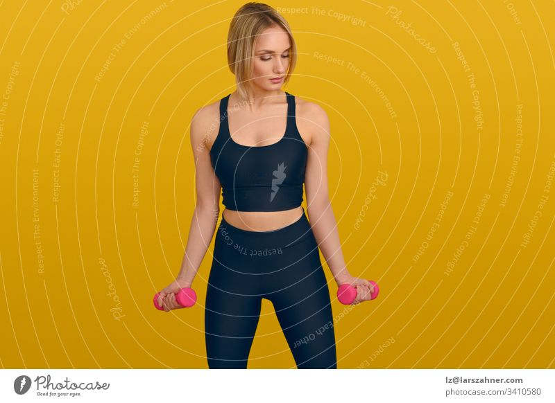 Young blond woman with dumbbells on yellow active attractive background beautiful black body clothes copyspace exercise fitness gymnastics hand hands health