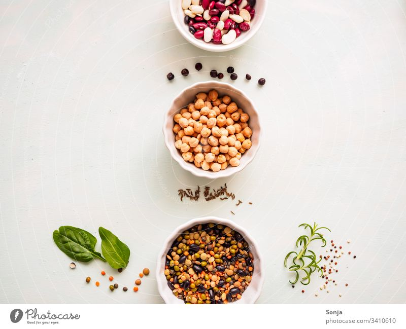 Chick peas and various legumes in white bowls in a row on a light kitchen table with spices, flat layer, vegetable protein, healthy food chickpea Bean Legume