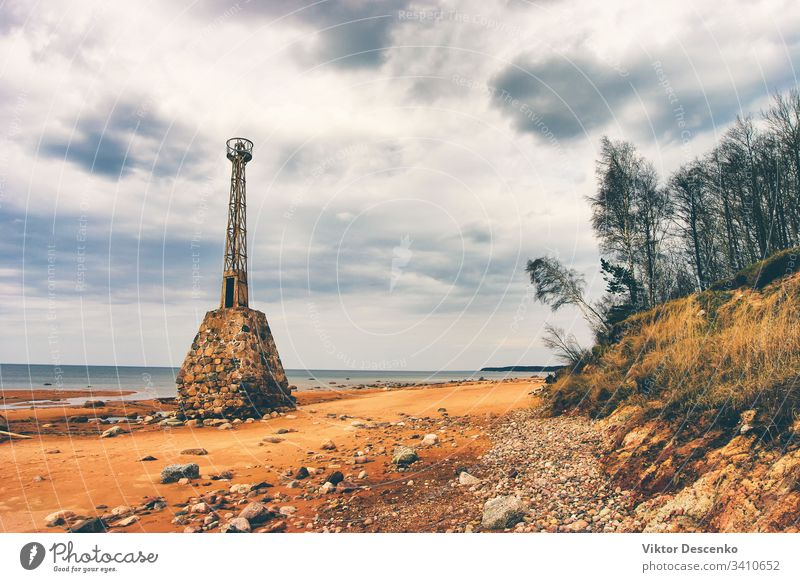 Old ruined lighthouse in the Baltic background beach water architecture moss navigation old outer port rocks shore stock striped structure tower travel tuja sea