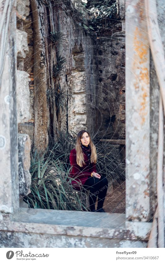 Woman sitting on the ruins of an antique church tourist abandoned building convent moss famous historical history national place rock monastery park art sun