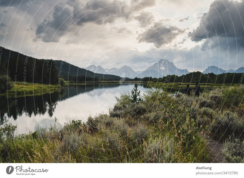 Mirror-smooth lake with green forests on the banks and steep snow-covered mountains in the background Authentic National Park Yellowstone National Park Sky