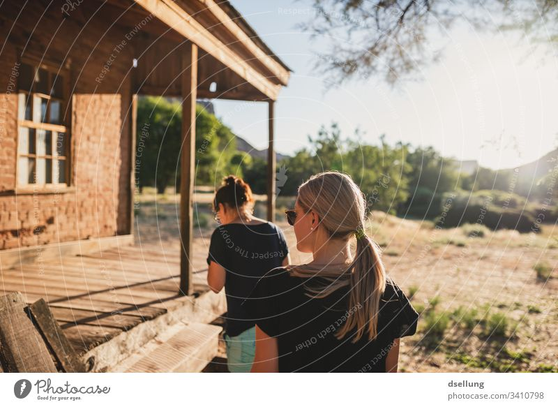 Two young women walk towards a wooden house in the evening light To enjoy recover relax Single-minded confident Future Forward Natural trees Plant Harmonious