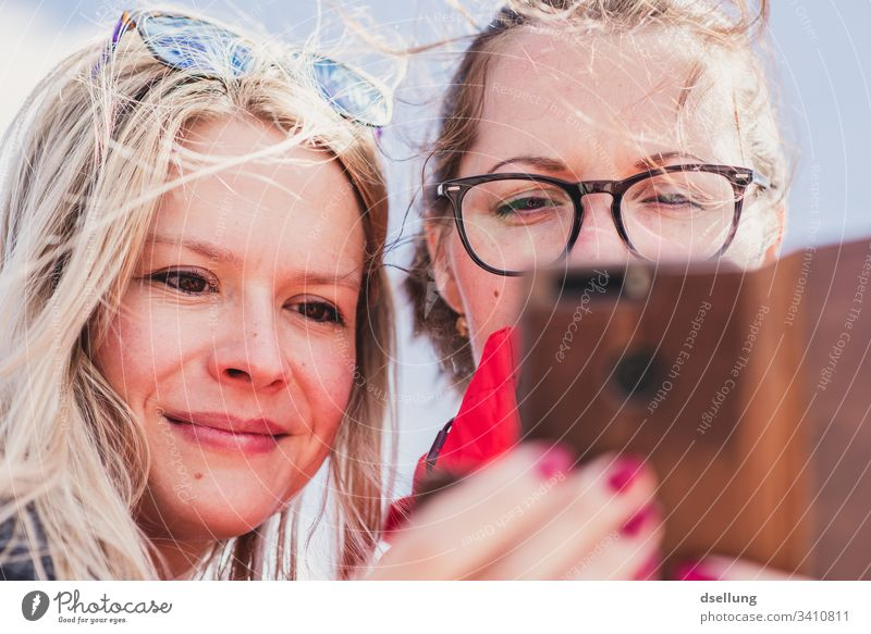 Two young women looking at a smartphone together Person wearing glasses Eyeglasses Ease relaxed Joie de vivre (Vitality) Self-confident Smiling Contentment