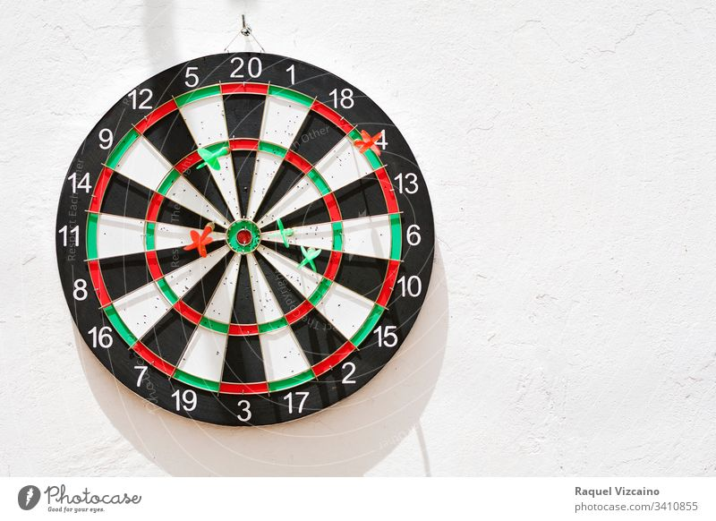 Diana with its green and red nailed darts, hanging on the white wall illuminated by the sun. target dartboard game sport isolated competition center success