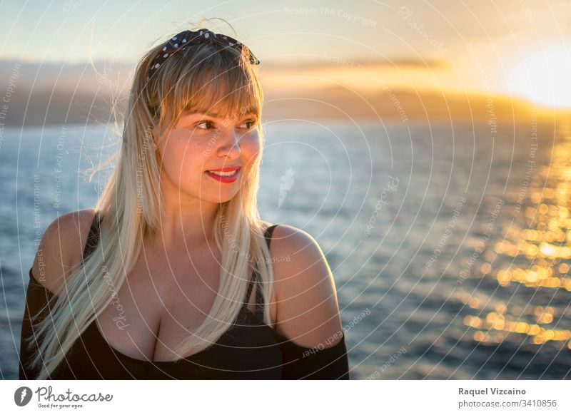 Portrait of a blonde woman with the sea in the background and lit by the evening sunlight. beach beautiful young beauty summer portrait sunset ocean happy hair