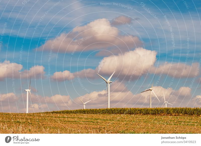 ecological renewable green energy wind power station on a field in evening sun alternative background blue change clean climate change cloud countryside